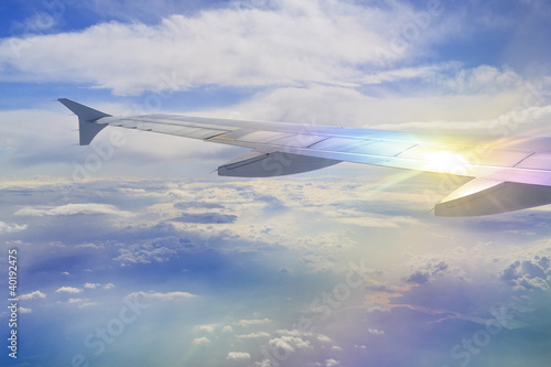 Fotografering Flugzeug-Flügel mit Lichtreflex über den Wolken