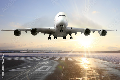 Passenger airplane landing on runway in airport. Evening Tablou Canvas