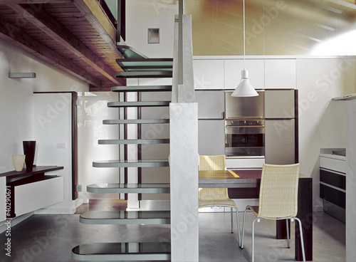 cucina moderna in mansarda e scala di vetro - Buy this stock photo ...