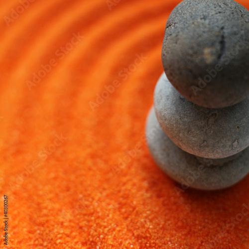 Photo sur Plexiglas Zen pierres a sable cailloux en équilibte sur sable de couleur orange