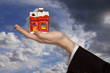 Hand of the Businessman with the House on the dramatically Sky