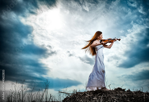Fotografia The red-haired girl with a violin outdoor