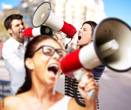 young friends screaming with megaphone against a building Canvas Print