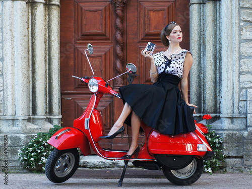 Photo  A young woman posing in a dress behind a scooter