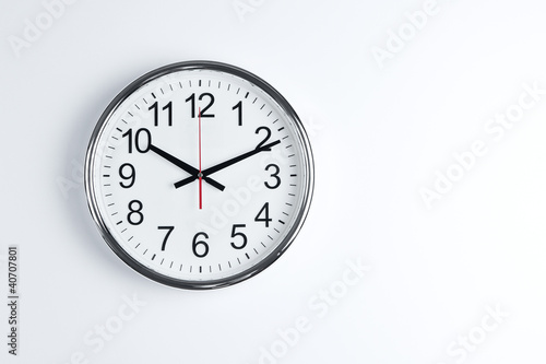Fotografía  Silver shiny clock hanging at the wall with copy space
