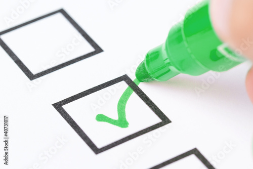 Fotografie, Obraz  Macro shot of human hand drawing green check mark in checklist b