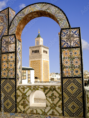 Poster Tunesië Mosque minaret framed by a tiled arch in Tunis city, Tunisia