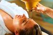 Leinwandbild Motiv Frau genießt eine Ayurveda Ölmassage