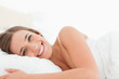 Woman lying in bed with a bright smile