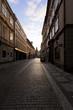 Dawns light reflects off windows and stones on Prague street