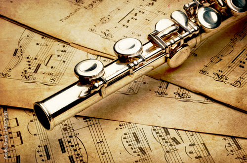 Photo Silver flute on an ancient musical background