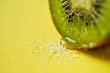 A slice of kiwifruit with sugar on yellow background