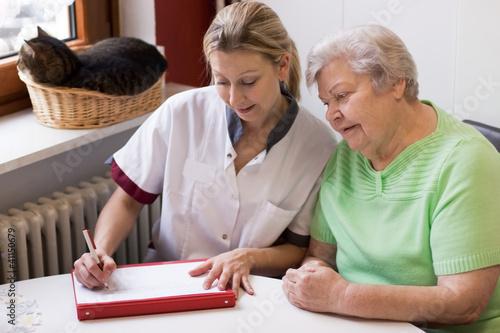 Fotografia  Altenpflegerin beim Hausbesuch einer Patientin