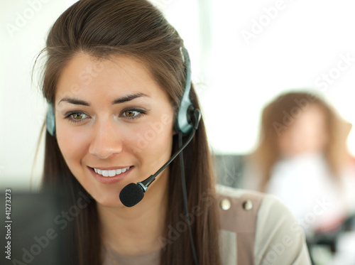 Fotomural  Female customer support operator with headset and smiling