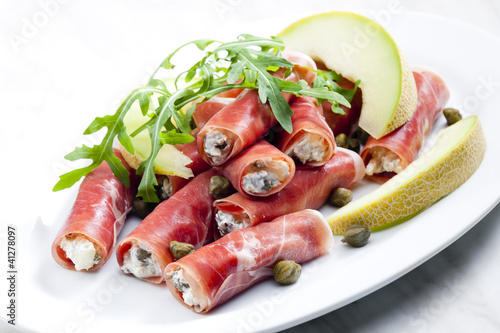Spoed Fotobehang Voorgerecht Parma ham rolls filled with cream cheese, Galia melon and capers