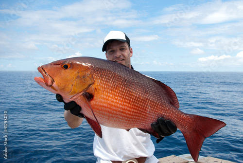Poster Fishing Happy fisherman holding a beautiful red snapper