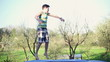 Happy young boy jumping on trampoline, slow motion