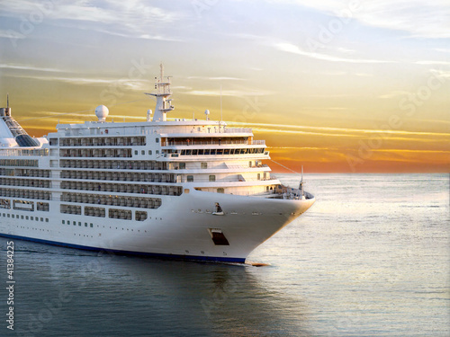 Fotografia  Luxury cruise ship sailing from port on sunset