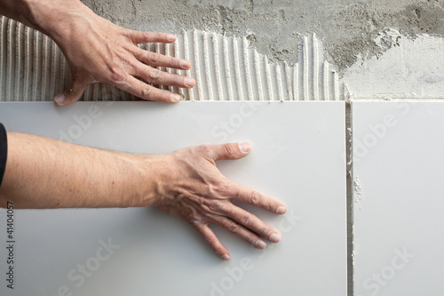 Photo construction mason man hands on tiles work