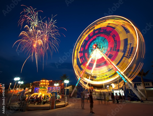 Foto op Plexiglas Amusementspark Amusement park at night - ferris wheel in motion and firework
