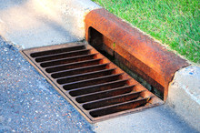 Storm Sewer By Footpath, Storm Drain System, Street Gutter With Rusty Cover