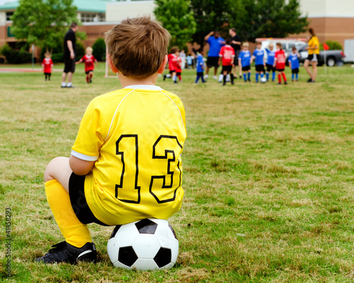 Photo  Boy  watching organized youth soccer game from sidelines