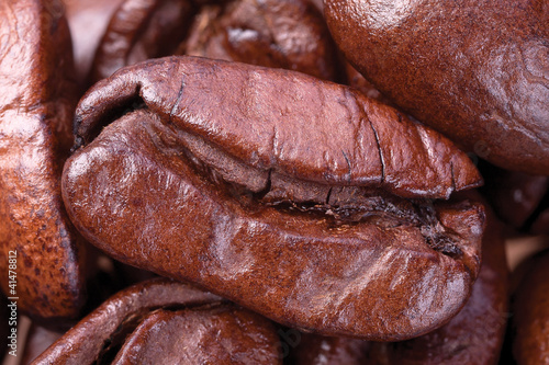 One brown grains of coffee close to the blurry background of cof