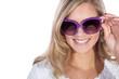 canvas print picture - Hübsche Frau blickt durch Sonnenbrille und lacht
