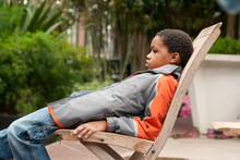 Bored Kid Slouching In A Chair