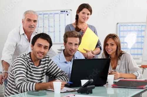 Fotografía  Class and teacher gatherd around laptop