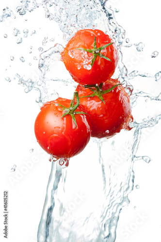 Poster Eclaboussures d eau Three Fresh red Tomatoes in splash of water Isolated on white ba