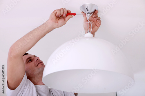 Man fixing ceiling light Canvas Print