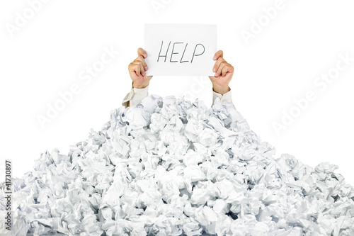 Fotografía  Person under crumpled pile of papers with a help sign / isolated