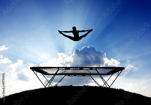 Foto-Stoff bedruckt - silhouette of female gymnast on trampoline in front of clouds (von Alex Koch)