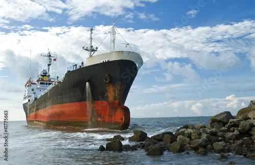 Cargo ship run aground on rocky shore shore Wallpaper Mural
