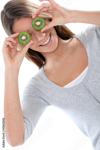Poster de jardin Bar Young woman smiling hiding her eyes with kiwi fruits