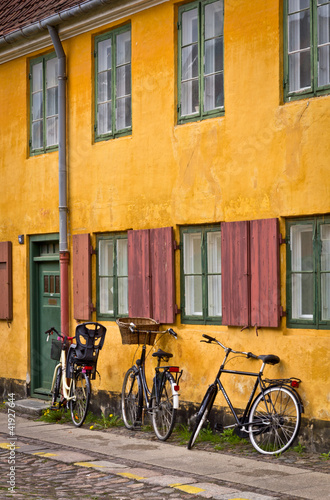 Photo  Bicycles standing next the traditional yellow building