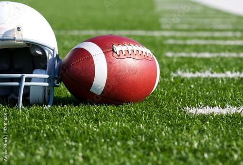 Fotografiet  Football and Helmet on the Field