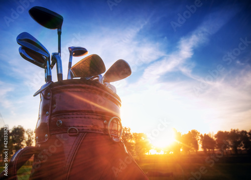Tuinposter Golf Golf gear, clubs at sunset on golf course
