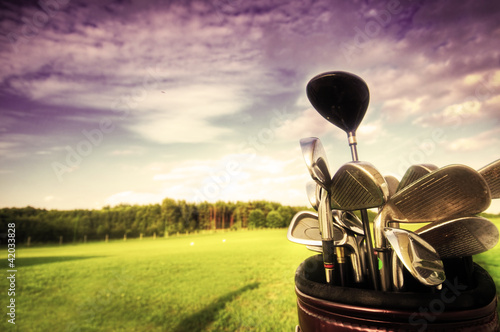 Fotobehang Golf Golf gear, clubs at sunset on golf course