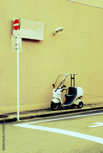 Motor scooters parked beside the wall with no entry sign