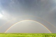 Vivid Double Rainbow Against A Green Field