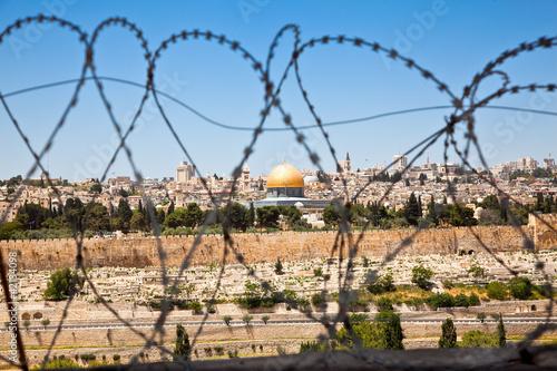 Foto auf Leinwand Mittlerer Osten The Old City of Jerusalem seen through coils of razor wire