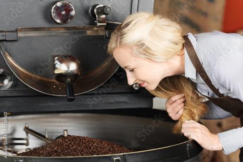 Fotomural  frau schaut auf geröstete kaffeebohnen