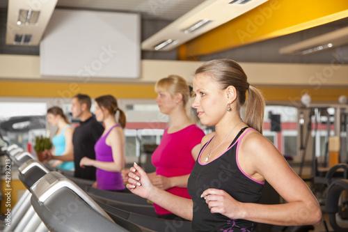 Fotografie, Obraz  junge Menschen beim Training auf Laufbändern im Fitnessstudio