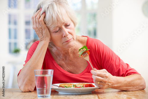 Photo Sick older woman trying to eat