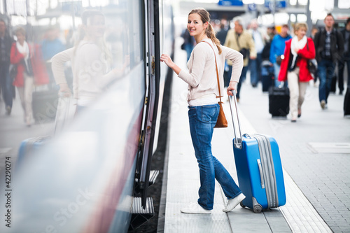 Pretty young woman boarding a train (color toned image) Poster Mural XXL