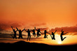 canvas print picture - silhouette of teenagers jumping in sunset on mountain range