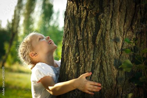 Fotografie, Obraz  Little girl hugging a tree, looking up