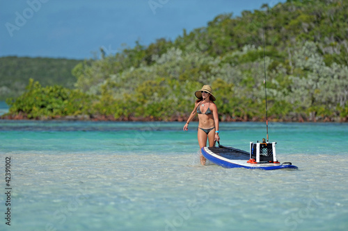 Printed kitchen splashbacks Fishing Woman pulling paddle board out to sea
